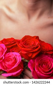Bouquet of bright fresh red roses on the background of the female chest and collarbone.