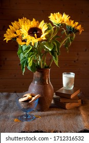 A bouquet of bright sunflowers in a clay jug, books, a glass of milk and a bowl of cookies on a rough tablecloth on a wooden background.