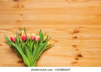 Bouquet of bright tulips on a wooden table, background