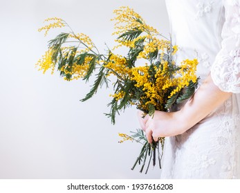 Bouquet of bright, yellow flowers in the hands of a young woman in a white dress. Isolated, close-up. Wedding preparations