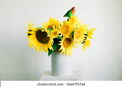 bouquet of bright yellow sunflower flowers with a lovebird parrot in a retro vase on a white background