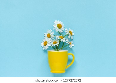 Bouquet chamomile daisies flowers in yellow mug on pastel blue color paper background Copy space Template for postcard, lettering, text or your design Flat lay Top view Concept Hello summer.