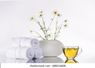 Bouquet of chamomiles flowers in a white vase and a transparent cup with tea on a white background.Towel, spa.
