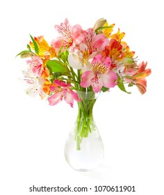 Bouquet of  colorful Alstroemeria flowers in a transparent glass vase isolated on white background.