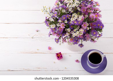 Bouquet of colorful aster flowers in a pitcher and cup of coffee on white vintage background with copy space