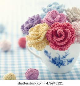 Bouquet of colorful crochet flowers in a vintage cup