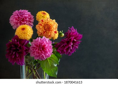 A bouquet of colorful Dahlia flowers in a vase on black textured background