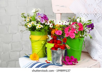 Bouquet of colorful flowers and fresh cherries in decorative buckets, on chair, on light wall background