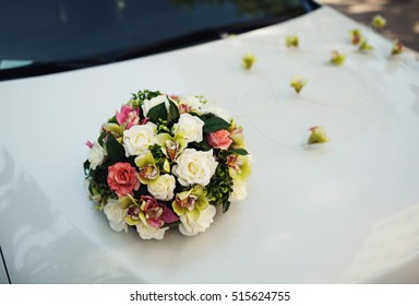 Bouquet of colorful flowers on the white wedding car