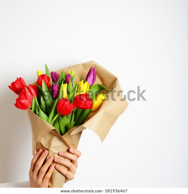 Bouquet of colorful tulips in female hands and kraft paper