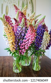 A bouquet of colourful lupins on a wooden table. Beautiful Interior decor.