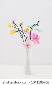 Bouquet of crepe paper cosmos and sweet peas in a vase on white