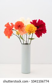 Bouquet of crepe paper marigold, poppies and roses flowers in a vase on white
