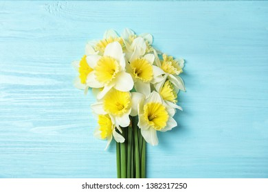 Bouquet of daffodils on wooden background, top view. Fresh spring flowers