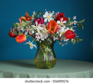 Bouquet of daffodils and tulips on the table to blue. Spring still life.