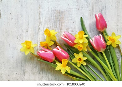 Bouquet of daffodils, tulips on wooden background