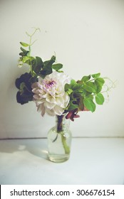 bouquet  with dahlia and sweet pea in glass bottle. low depth of field. instagram toned.