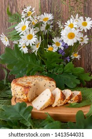 a bouquet of daisies with oak and a branch with smoked cheese on a wooden table. Celebration of a traditional holiday in Latvia Ligo in June