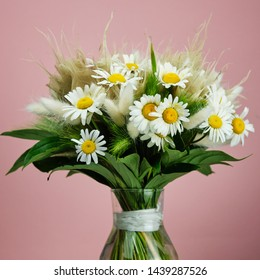 bouquet with daisies on a pink background