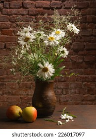 Bouquet of daisies in vase and apples