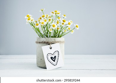 Bouquet of daisy-chamomile flowers in concrete pot in the morning  with  hand drawn doodle heart on the gift tag.