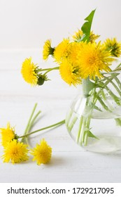 A bouquet of dandelions in white vase on a white wooden background, with copy space