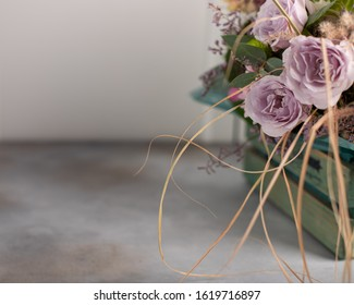 bouquet of delicate lilac roses in a wooden vintage box. spring greeting card. side view, copy space