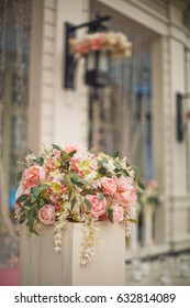 Bouquet of delicate pink roses stands on white pillar