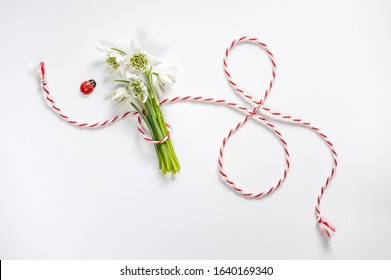 Bouquet of delicate snowdrops on white background. Number 8 made of red-white rope.   Postcard for March 8 with the decor of flowers. Women's Day concept. Soft focus