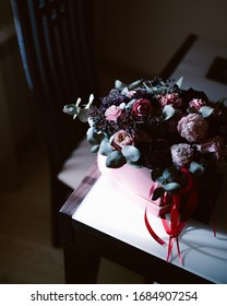 A bouquet of different flowers on the edge of the table. Creative high quality photo for decoration purposes or flower stores and shops in pink tones