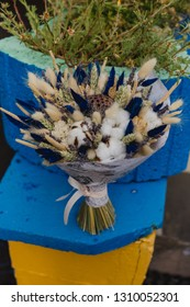 Bouquet of dried flowers in blue and yellow tones. Bouquet in the package. Festive bouquet. Cotton flowers, lotus flower, wheat, lavender.