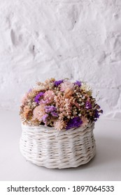 Bouquet of dried immortelle flowers on a white background in the basket. Interior decor. Multi-colored composition. Place for copy-space text. Trend. Winter wedding bouquet. long bloom, minimalism