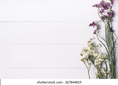 Bouquet of dried wild flowers on a white background of vintage wooden planks top view horizontal