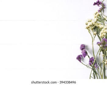 Bouquet of dried wild flowers on white table background  with natural wood vintage planks wooden texture top view horizontal, empty space for publicity information or advertising text