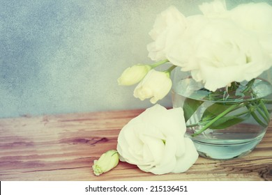 Bouquet of eustoma flowers in vase on wooden table.