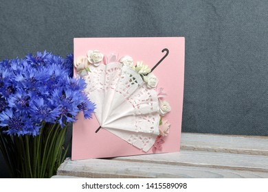 Bouquet field cornflowers and a greeting card.  On a gray background. Cornflower or Blue (Centaurea cyanus), with spider-woolly linear-lanceolate leaves and blue flowers.