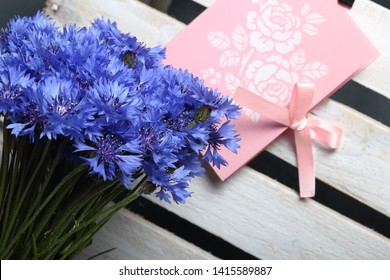 Bouquet field cornflowers and a greeting card. Cornflower or Blue (Centaurea cyanus), with spider-woolly linear-lanceolate leaves and blue flowers.