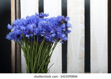 Bouquet field cornflowers. On the background of wooden boards. Cornflower or Blue (Centaurea cyanus), with spider-woolly linear-lanceolate leaves and blue flowers.