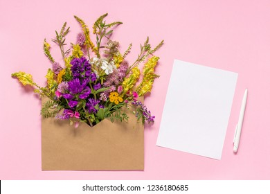 Bouquet of field multicolored flowers in craft envelope and white empty paper card for text with pen on pink background. Greeting card Flat Lay Mock-up Concept Women's day or Mothers Day.