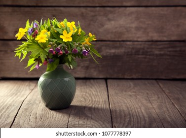 bouquet of field wild flowers in a vase on old boards.