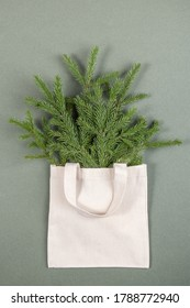 A bouquet of fir branches in a fabric eco bag on a green background. Concept eco-friendly and zero waste. Top View Flat lay.