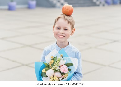 bouquet for first beloved teacher on first of September. Flowers for the last bell. day of knowledge. beginning of the school year. first-graders in a school uniform on the background of school