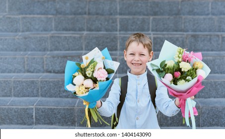 a bouquet for first beloved teacher on first of September. Flowers for the last bell. day of knowledge. beginning of the school year. first-grader with bouquet in a school uniform on the backg