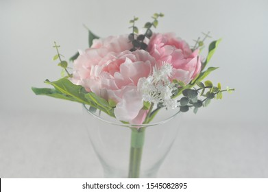 a bouquet of flower in vase with light grey background