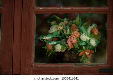 a bouquet of flowers being displayed by a window side