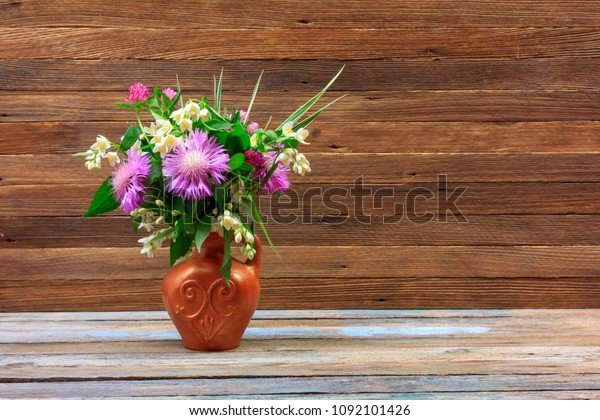 bouquet of flowers of clover, cornflowers and Jasmine in a earthenware jug on a wooden table on a brown retro background with a copy space