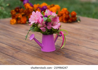 bouquet of flowers in a decorative watering can, on a wooden background