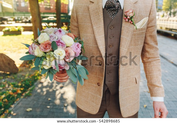 a bouquet of flowers in hand of man