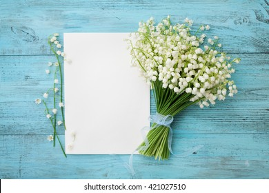Bouquet of flowers lily of the valley and empty paper sheet on turquoise rustic table from above, beautiful vintage card, top view, space for text, flat lay.