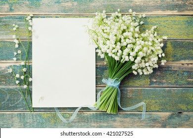 Bouquet of flowers lily of the valley and empty paper sheet on rustic table from above, beautiful vintage card, top view, copy space for text, flat lay